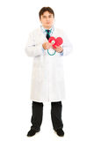 Doctor holding stethoscope on paper heart Stock Image
