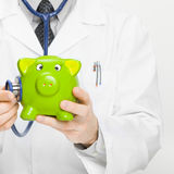 Doctor holding stethoscope and piggybank Stock Photos