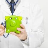 Doctor holding stethoscope and piggybank Stock Photos