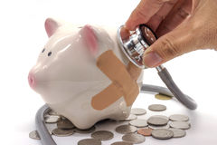 Doctor Holding Stethoscope to Piggy Bank Royalty Free Stock Images
