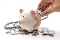 Doctor Holding Stethoscope to Piggy Bank Royalty Free Stock Photos