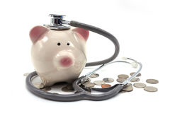 Doctor Holding Stethoscope to Piggy Bank Stock Photo