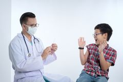 Doctor holding a syringe with injection vaccination. Boy is afra Royalty Free Stock Images