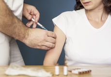 Doctor holding a syringe and vaccinating a woman a Royalty Free Stock Images