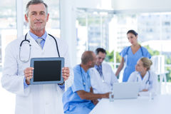 Doctor holding tablet computer while his colleagues works Royalty Free Stock Image