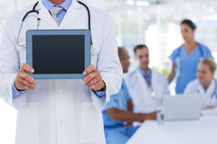 Doctor holding tablet computer while his colleagues works Stock Photos