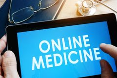 Doctor holding tablet with online medicine. Doctor holding tablet with words online medicine Stock Photo