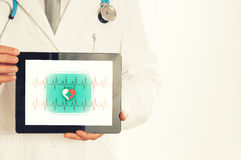 Doctor holding tablet pc with media illustration. stock photos