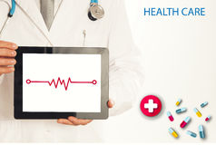 Doctor holding tablet pc with media illustration. stock photography