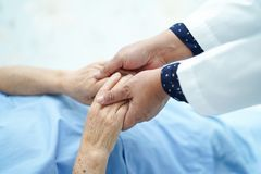 Doctor holding touching hands Asian senior or elderly old lady woman patient with love, care. Doctor holding touching hands Asian senior or elderly old lady royalty free stock image