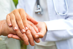 Doctor holding trembling hand Stock Photo