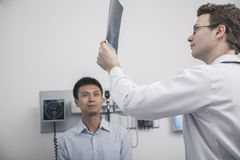 Doctor holding up and looking at x-ray of patient Stock Image