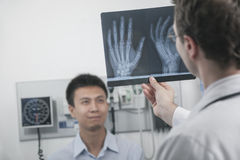 Doctor holding up and looking at x-ray of patients hand bones, patient in the background Royalty Free Stock Photo