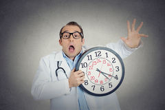 Doctor holding wall clock running out of time stock photography