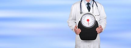 Doctor holding a weight scale. On blurred background royalty free stock images
