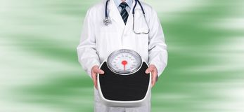 Doctor holding a weight scale. On blurred background royalty free stock photo