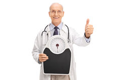Doctor holding a weight scale Royalty Free Stock Photo
