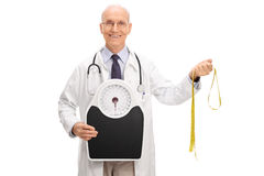 Doctor holding weight scale and measuring tape Royalty Free Stock Photography