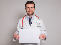 Doctor holding a white cardboard banner. On gray background Royalty Free Stock Images