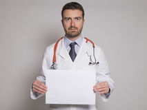 Doctor holding a white copyspace billboard i Stock Images