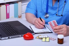 The doctor holds a blister with pills in his hand and writes out the prescription in the workplace close-up. prescribe. Medicines, a legal pharmacy store royalty free stock images