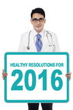 Doctor holds board with healthy resolutions for 2016 Stock Photos