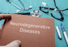 Doctor holds book on neurodegenerative Diseases in a hospital stock image