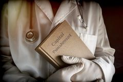 Doctor holds in a Capital Punishment book in a hospital. Conceptual image Royalty Free Stock Photo