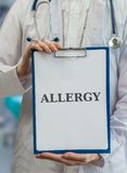 Doctor holds clipboard with allergy diagnosis Royalty Free Stock Photos