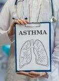 Doctor holds clipboard with asthma diagnosis and lungs drawing Royalty Free Stock Image