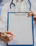 Doctor holds clipboard with sheet of paper as frame for signatur Royalty Free Stock Photos