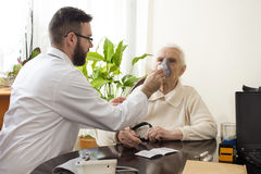The doctor holds inhaler the face of an old woman. Inhalation of the upper respiratory tract Stock Photos