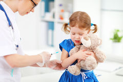 Doctor holds an injection vaccination child Stock Photos