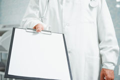 Doctor holds out empty clipboard, copy-space Royalty Free Stock Photos