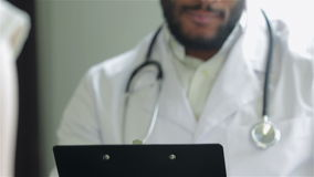 A doctor holds a paper holder and writes stock footage