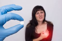 Doctor holds pill in hand from cardiovascular system, patient girl stands in the background and holds on to heart, heart problems. royalty free stock photography