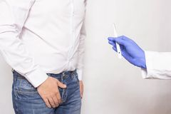 A doctor holds a surgical scalpel against the background of a man whose prostate cancer concept of prostate gland. Surgery using a prostatectomy, inflammation royalty free stock photos