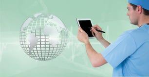 Doctor (hombres) usando su tableta mientras que él mira la tierra metálica 3D Imágenes de archivo libres de regalías