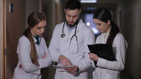 Doctor in hospital corridor interns explains that a patient receives. Doctor with two girls interns parses the diagnosis stock footage