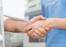 Doctor in hospital handshake with another doctor. Healthcare people teamwork and medical service concept royalty free stock images