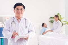 Doctor at hospital. Mature doctor at his patient's ward Royalty Free Stock Photography