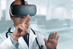Doctor in a hospital pointing his finger on a virtual screen. Doctor with virtual reality glasses simulating working on a virtual interface and in the background Royalty Free Stock Image
