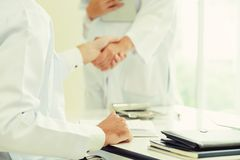 Doctor at hospital shakes hand with another doctor. Doctor at the hospital giving handshake to another doctor showing success and teamwork of professional royalty free stock image