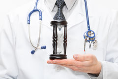 Doctor with hourglass in hand Stock Images