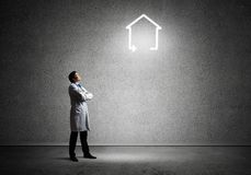 Doctor with house symbol. Conceptual image of successful doctor in white medical suit interracting with glowing house symbol while standing against gray dark stock photos