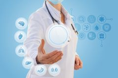 Doctor with icons of internal organs . Doctor with icons of internal organs on a blue background royalty free stock image
