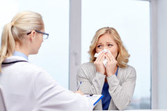 Doctor and ill woman patient with flu at clinic Royalty Free Stock Photo
