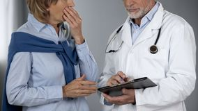 Doctor informing lady about her sick relative, woman shocked at bad news royalty free stock image