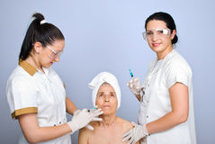 Doctor inject botox to senior cheek woman Stock Images