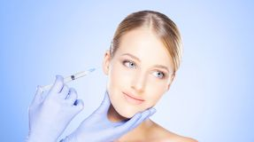 Doctor injecting in a beautiful face of a young woman. Plastic s. Urgery concept stock photography